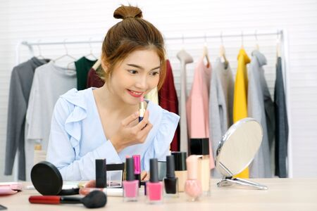 Young beautiful asian woman beauty blogger applying makeup smile and look at camera, portrait of asian attractive female holding lipstick and cosmetic products with happiness