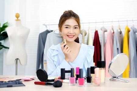 Young beautiful asian woman beauty blogger applying makeup smiling and look at camera, portrait of asian attractive female holding lipstick and cosmetic products with happiness, people and beauty fashion lifestyle