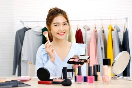 Young beautiful asian woman beauty blogger applying makeup smiling and look at camera, portrait of happy asia attractive female holding brush and cosmetic products at studio, people and beauty fashion small business lifestyle Фото со стока - 129901709