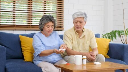 Senior asian couple take pill medicine for elderly health care while sitting on sofa, Retirement couple take vitamin pill, Senior asian medication and health care concept 写真素材 - 129902225
