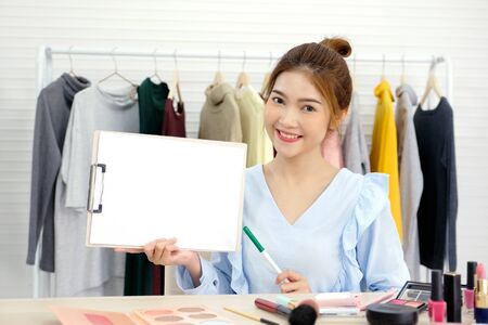 Young beautiful asian woman beauty blogger holding blank white chart board while applying makeup smiling and look at camera, Happy asian female and cosmetic products vlogger Фото со стока - 129902386
