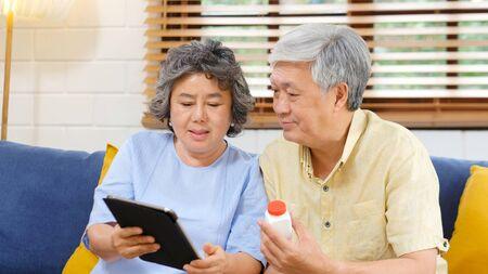 Senior Aziatisch stel met fles pil met behulp van digitale tablet om videoconferentiegesprek te voeren met arts, apotheekadvies over medische gezondheidszorg voor pensionering, ouderen, ouderen en technologie Stockfoto
