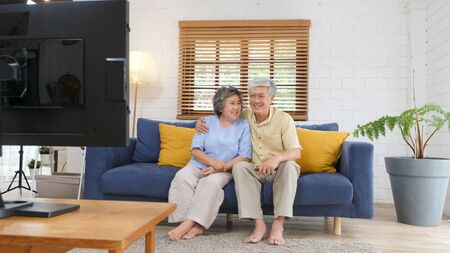 Senior asian couple holding remote control while watching television in home living room with happiness, old people retirement routine lifestyle