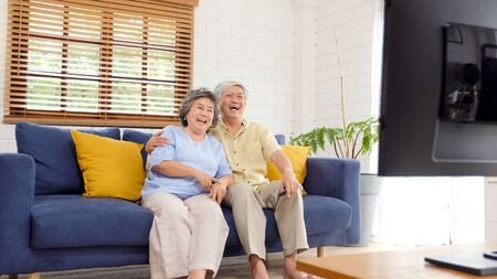 Senior asian couple watching television in home living room with happiness, old people retirement routine lifestyle Stok Fotoğraf