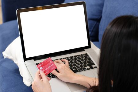 Woman hands holding credit card and typing laptop computer with blank screen for mock up template background, Shopping online, internet banking payment concept