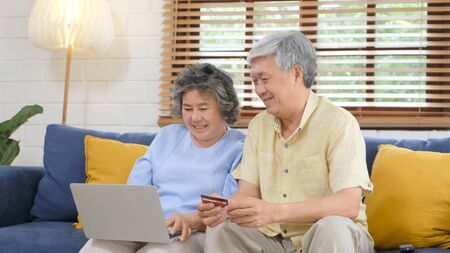 Senior asian couple shopping online by using laptop computer and credit card at home living room, Retirement people technology lifestyle Stock Photo
