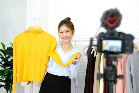 Youn asian woman fashion blogger showing cloth with smiling face while recording new content for vlog and fashion online shopping with camera at home studio Standard-Bild