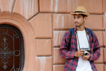 Portrait of young asian man tourist backpacker holding vintage camera while traveling around city in summer vacation