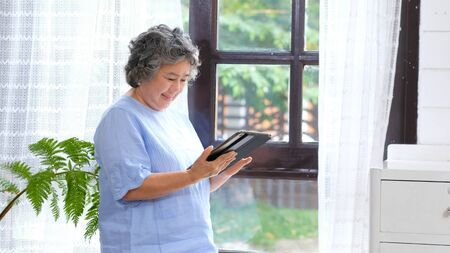 Senior asian woman using digital tablet computer at home background, Retirement asian woman and digital tablet standing by home window, Active senior people and technology lifestyles 写真素材