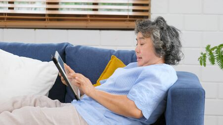 Senior asian woman using digital tablet computer, Retirement asian woman and digital tablet while lying on sofa at home living room, Active senior people and technology lifestyles