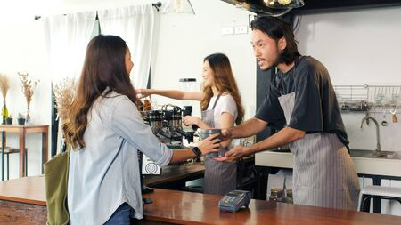 Zero waste concept, Asian woman customer giving her own coffee cup to barista, waiter, for buying takeout coffee at cafe counter