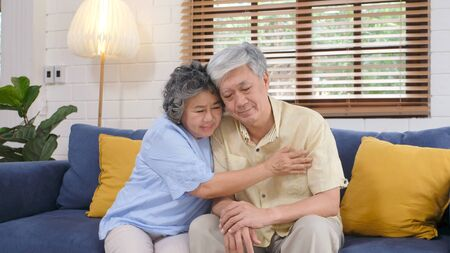 Senior asian couple comforting each other from depressed emotion while sitting on sofa at home living room, old retirement lifestyle