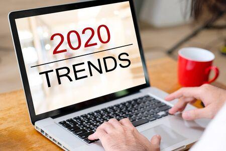 Tendances numériques 2020, main d'homme attachant un ordinateur portable avec des tendances 2020 sur fond d'écran, concept de marketing numérique, d'entreprise et de technologie