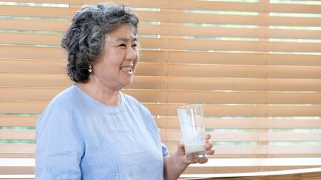 Senior asian woman drinking milk at kitchen home in the morning, Elderly asia female holding glass of milk for dairy breakfast, Retirement people healthy lifestyle