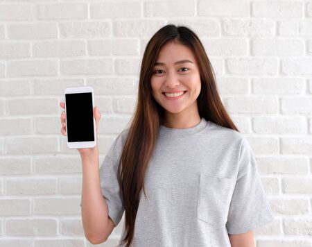 Young asian woman holding smart phone with blank on screen for mock up looking at camera and smiling while standing over white wall background, asia people and technology template