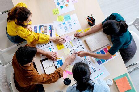 Lluvia de ideas sobre cómo planificar el trabajo en equipo asiático creativo, reunión del equipo de desarrolladores de aplicaciones de teléfonos móviles del Grupo de Asia para obtener ideas sobre el diseño de prototipos de teléfonos inteligentes de visualización de pantalla, ux startup, pequeñas empresas, vista superior Foto de archivo