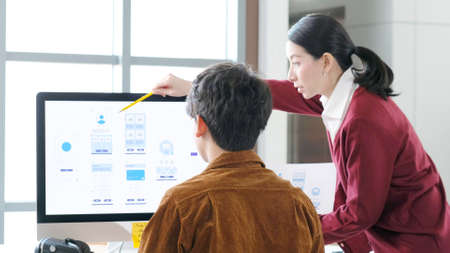 Website designer, Creative planning phone app development template layout framework wireframe design, User experience concept, Young asian woman and man UX designer working on smartphone application at office