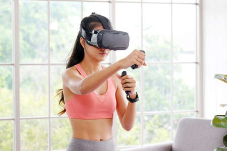 E sport, Happy asian woman wearing virtual reality headset for interactive excercise at home, Asia girl playing vr while workout fitness, Female and wearable technology