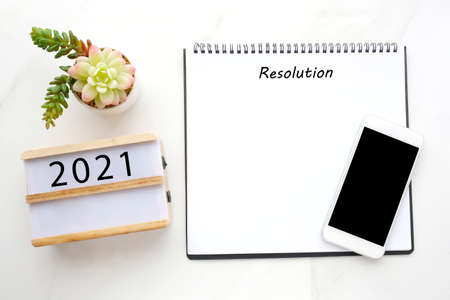 2021 resolution on blank notebook paper, smart phone with blank screen on white marble background, 2019 new year mock up, template, flat lay