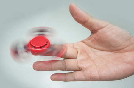 Red Hand spinner,fidgeting hand toy rotating on man's finger