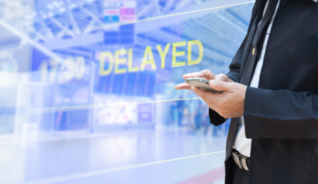 business man use smartphone with airport blur background,delayed flight 免版税图像