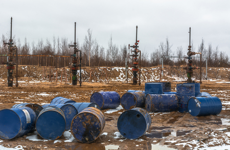 Empty barrels from the oil before the stopped oil wells. Ecological problem in the field.