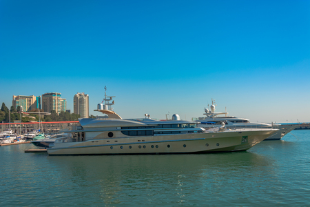 Port morski w lecie. W marinie stoi wiele różnych jachtów i łodzi. Żeglarze i podróżnicy przygotowują się do wypłynięcia w morze. W tle budynek nadmorskiego miasta.