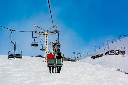 Extreme cable car ride. Winter holidays in the mountains. Snow-covered mountain slopes. Skiers and tourists.