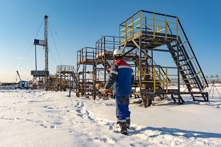 Oilman, is on the northern field along oil producing wells. In the background, a drilling rig. Winter. Sunny day. Banco de Imagens - 121633011