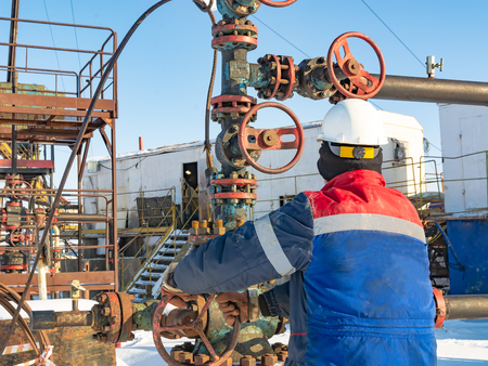 An employee of an oil company performs work on the well. Rotates the steering wheel on the fountain fittings. In the background equipment for oil production. Winter day at the polar oil field. Banco de Imagens - 121633059