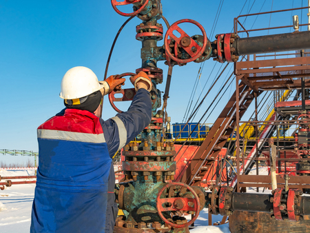 An employee of an oil company performs work on the well. Rotates the steering wheel on the fountain fittings. In the background equipment for oil production. Winter day at the polar oil field. Banco de Imagens - 121633061