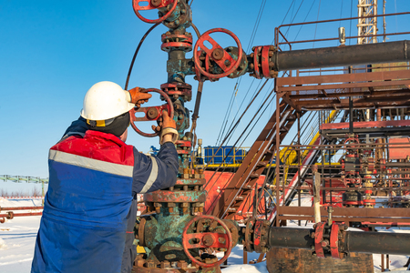 An employee of an oil company performs work on the well. Rotates the steering wheel on the fountain fittings. In the background equipment for oil production. Winter day at the polar oil field.