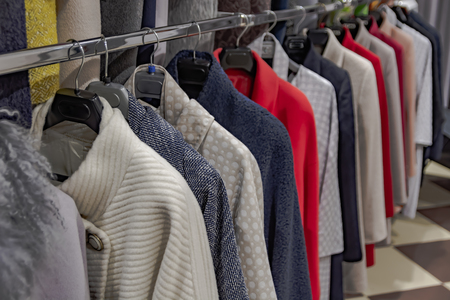 Multicolored clothes hanging on hangers in a row. Coats of different styles are stored in the dressing room or shop window. Background color composition with a blurred perspective.