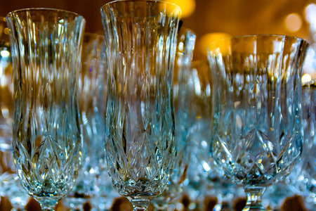 The play of light on beautifully shaped crystal glasses. Some items are out of focus. Blurred background Multicolored spots of reflected light.