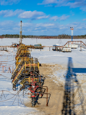Oil production wells are located in a row in an oil field in western Siberia. In the background, the well is being repaired. On the ground, the shadow of the rig. Spring sunny day. Stock Photo