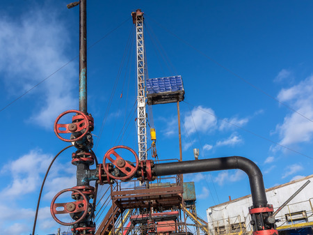 Fountain valves for oil production in the background of the drilling rig. Round wheel to regulate the flow of oil from the well. Spring sunny day in western Siberia. Stock Photo