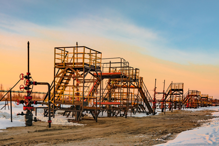 Oil production wells are located in a row at an oil field in western Siberia. Sunset spring sunny day.