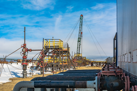 Oil field in Siberia. In a row are oil producing wells. In the background, work is underway to overhaul the well. In the foreground is a manifold with valves.