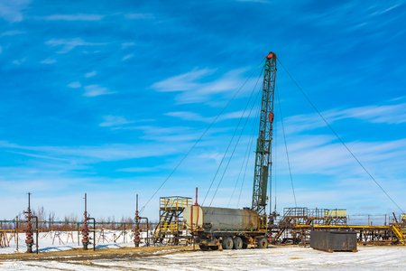 Oil field in Siberia. In a row there are oil producing wells. In the background, work is underway to overhaul the well. Spring. On the ground are the remains of snow.
