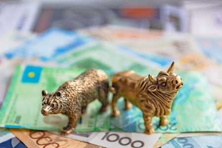 Bronze figures of a bull and a bear on the background of paper money and metal coins. Blur background and perspective. Concept and symbol of stock exchange and stock trading.