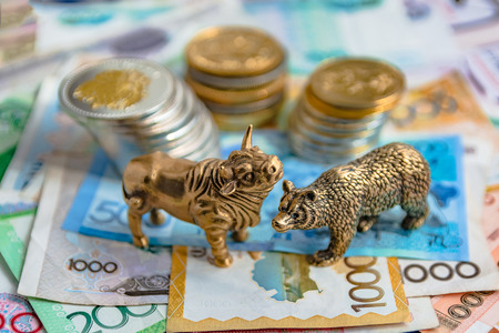 The bronze bull and bear figurines are arranged with paper money and metal coins. Blur background. Symbol and concept of trading on the stock exchange.