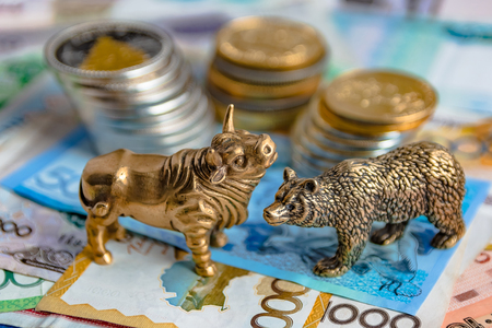 The bronze bull and bear figurines are arranged with paper money and metal coins. Blur background. Symbol and concept of trading on the stock exchange. Reklamní fotografie