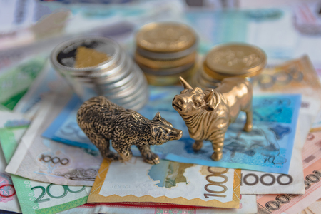 The bronze bull and bear figurines are arranged with paper money and metal coins. Blur background. Symbol and concept of trading on the stock exchange. Stockfoto
