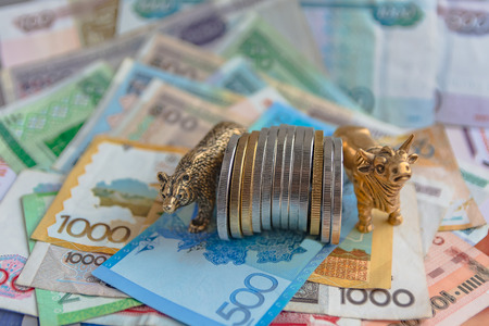 Bronze figures of a bull and a bear near metal coins on the background of paper money. Blur background and perspective. Concept and symbol of stock exchange and stock trading.