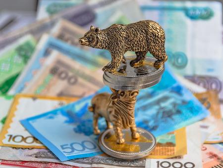 Bronzefiguren eines Stiers und eines Bären in der Nähe von Metallmünzen auf dem Hintergrund von Papiergeld. Hintergrund und Perspektive verwischen. Konzept und Symbol der Börse und des Aktienhandels.