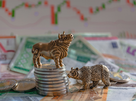 Bronze figures of a bull and a bear near metal coins against the background of paper money and charts. Blur background and perspective. Concept and symbol of stock exchange and stock trading.
