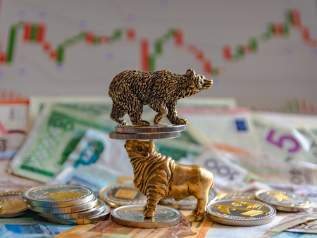 Bronze figures of a bull and a bear near metal coins against the background of paper money and the diagram of a trading terminal. Blur background and perspective. Concept and symbol of stock exchange and stock trading.