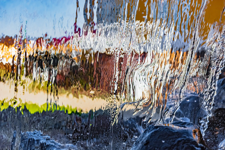 Blurred image formed by a falling wall of water. A variety of water figures in the waterfall. Translucent background of multicolor abstract aqua image.