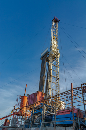 The design of the drilling rig for deep drilling in oil and gas against a blue sky. Many drill pipes installed vertically.