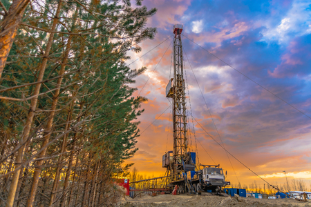Drilling a deep well mobile drilling rig in an oil and gas field. The field is located in the Far North in the taiga. Beautiful dramatic sunset sky in the background. Stok Fotoğraf